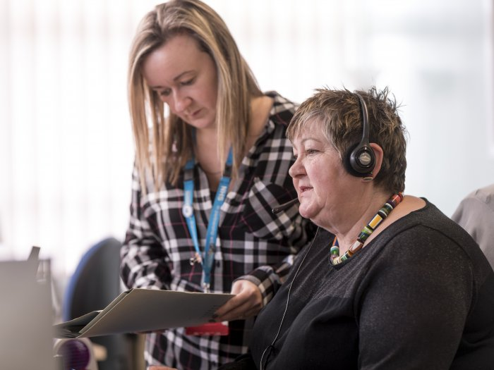 woman looking at notes with woman with headset