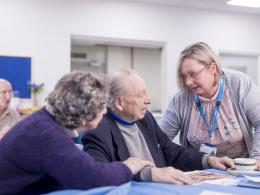 Woman clinician medic talking to an elderly man and woman